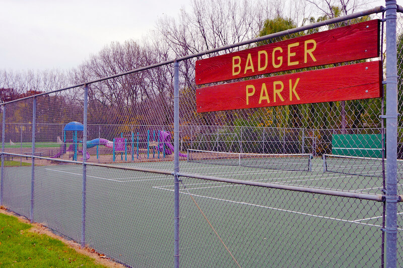 "sign reading ""Badger Park"" on fence around tennis courts"